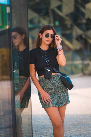 Lifestyle of a young Entrepreneur Caucasica brunette outside the office building. With green skirt and sunglasses