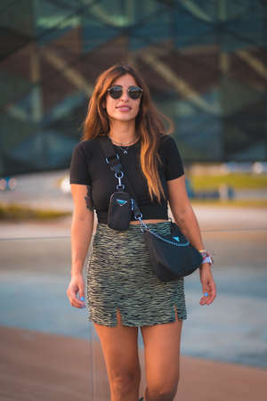 Beautiful young brunette caucasian businesswoman outside the background office building. With green skirt and sunglasses walking