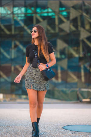 Lifestyle of a young caucasian brunette businesswoman outside the office building walking. With green skirt and sunglasses 版權商用圖片