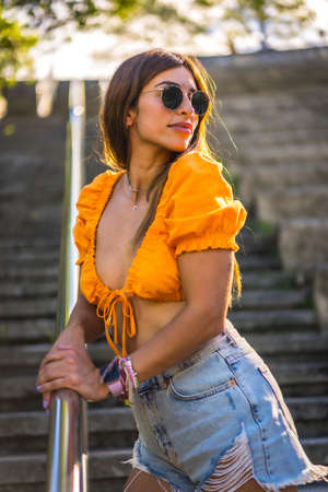 Lifestyle of a young caucasian brunette walking in the summer in a park in the city. Girl with seductive look on the stairs of the park 版權商用圖片