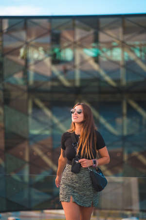 Beautiful young caucasian brunette businesswoman outside the green glass office building background. With Sunglasses And Looking, Vertical Photo