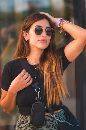 Beautiful young brunette caucasian businesswoman outside the office building walking. With green skirt and sunglasses looking for the sides