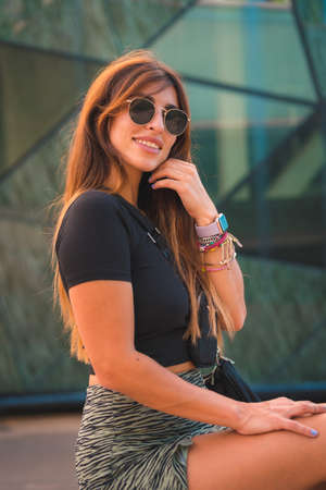 Street Style of an attractive young caucasian brunette in the city with sunglasses, on beautiful green crystals background smiling and looking, t-shirt and black boots 版權商用圖片