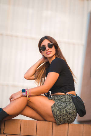 Street Style of an attractive young caucasian brunette sitting in the city with sunglasses, enjoying a veranao with a white wall background, vertical photo