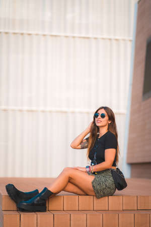 Street style of a young caucasian brunette sitting in the city enjoying verana with a white wall background