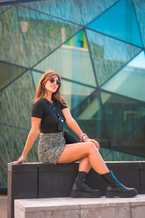 Street Style of an attractive young caucasian brunette in the city with sunglasses, posing on beautiful green crystals background 版權商用圖片