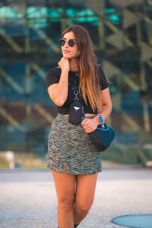 Lifestyle of a young caucasian brunette businesswoman outside the office building walking. With green skirt and sunglasses looking for the sides 版權商用圖片