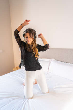 Young man with headphones dancing and enjoying music on top of bed 版權商用圖片