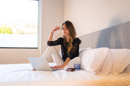 Young blonde Caucasian woman sitting on the bed at home with laptop watching the news online