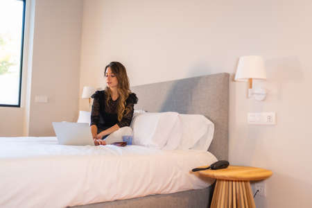 Young blonde Caucasian woman sitting on the bed at home with laptop watching online news and social networks 版權商用圖片
