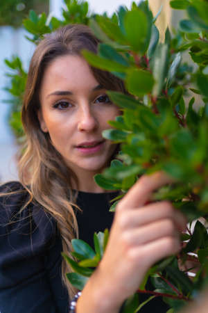 Portrait of a young blond Caucasian woman next to some green plants in spring