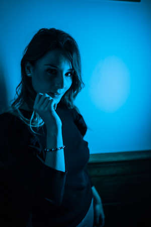 Portrait of a young woman looking at camera with blue led lights from the side