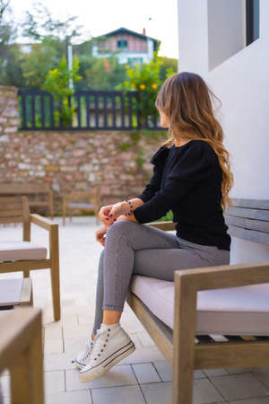 Portrait of a young blond Caucasian woman sitting on the terrace of a restaurant, vertical photo