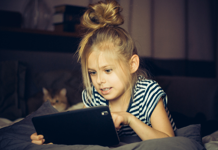 annoyed girl: Girl looks annoyed tablet with cat