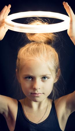 holding aloft: Beautiful girl gymnast holding aloft a glowing circle S