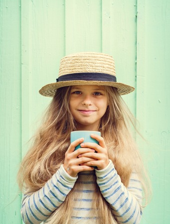 boater: Cute little girl stands near a turquoise wall in boater hat and holding cup. Space for text.Negative speace