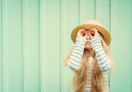 La petite fille mignonne se tient près d'un mur turquoise en canotier et des jumelles et semble inventé. Espace pour le texte. Speace Négatif.