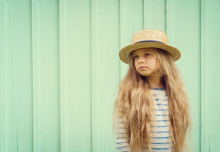boater: Cute little girl stands near a turquoise wall in boater hat and pensively looks aside. Space for text. Negative space.