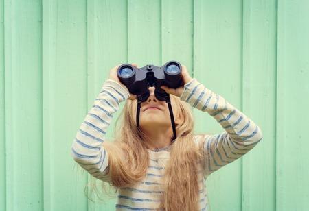niños rubios: Niña linda que se coloca cerca de una pared de color turquesa y se ve prismáticos. Espacio para text.Negative speace. Foto de archivo