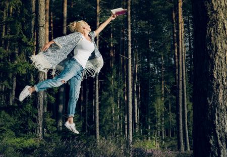 hermosa mujer joven que lee un libro y levita en el bosque. estilo de vida relajado.