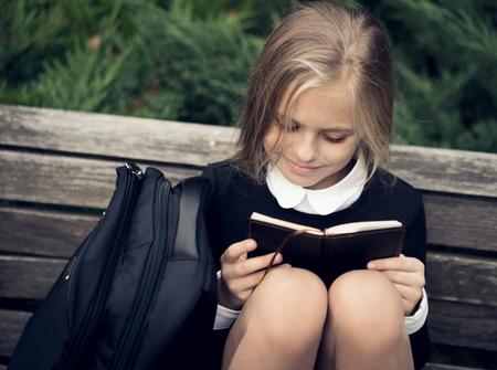 diligente: Hermosa chica rubia en un uniforme escolar se sienta en un banco del parque y leer un libro. uniform.Education la escuela Foto de archivo