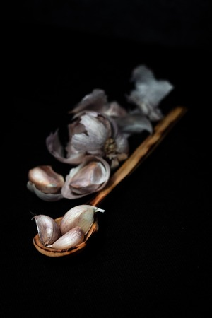 garlic on wooden spoon in low key