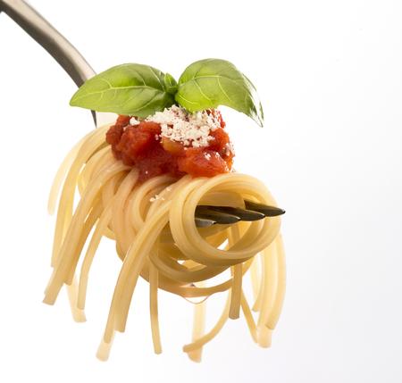 白い背景で隔離のスパゲッティとトマトのソースとフォーク
