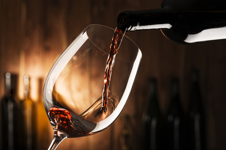 glas met rode wijn op houten achtergrond Stockfoto
