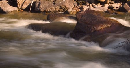 reaches: Fast flowing Spring melt off as golden evening light reaches the base of the St. Vrain river canyon in Colorado. Stock Photo