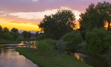 poudre river: A glowing sky above and on the Poudre River as it leaves the Rocky Mountains in Colorado.