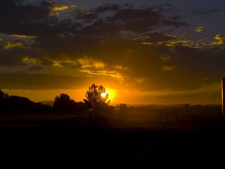 A sunset image of a dusty field from the Eastern plains of Colorado in front of the foothills of the Rocky Mountains.