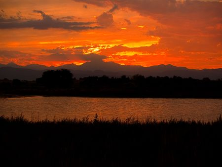 A flaming stormy sunset sky over a small lake, Longs Peak, and the Front Range of the Rocky Mountains.