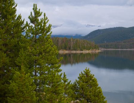 lake dillon: Evergreens and fog frame the still surface of Lake Dillon in the Colorado Rockes, Stock Photo