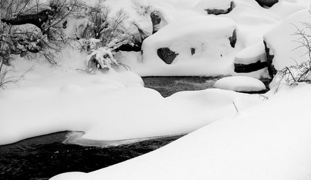 drifts: Snow drifts create unusual shapes over the boulders of a mountain river in Colorado.