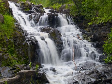 A waterfall surrounded by green spring vegetation in Northern Minnesota Stock Photo