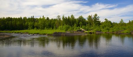 north woods: Forest of the North Woods of Minnesota across the reflection of a still river.
