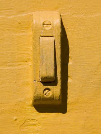 Een deurbel op een muur geschilderd geel.
