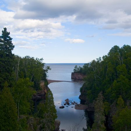 as: Mouth of the Baptism river in a still peaceful moment as it enters into Lake Superior Stock Photo