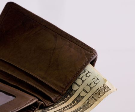 A brown wallet and three twenty dollar bills protruding from it.