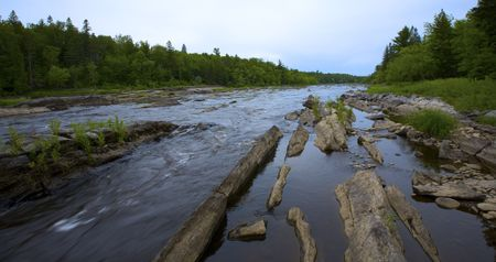 Looking upstream as a river rushes through stone  in the North Woods of Minnesota. 版權商用圖片