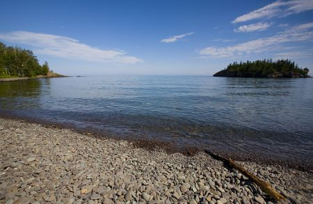 Island and a Northern bay off a rocky beach on the shore of Lake Superior