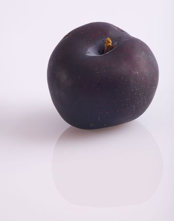 A plum reflecting on a white surface.