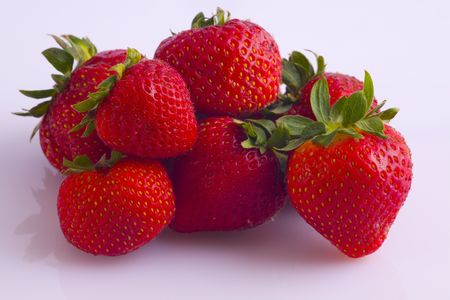 Aardbeien rood, dik en sappig, in een kleine hoop op een witte achtergrond.