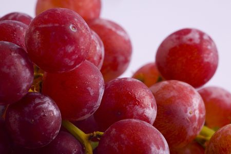 A close up image of red grapes connected to a stem