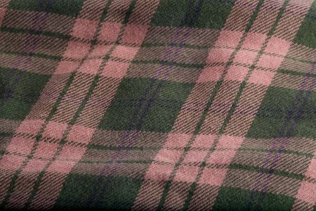 A folded flannel pattern of green and tan. Imagens