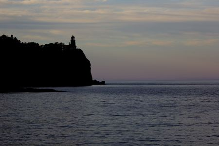 A lighthouse silhouette on a cliff overlooking Lake Super. Stock Photo - 3403863