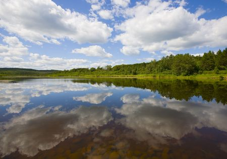 Mirror of clouds and forest  on the surface of a lake in the North Woods of Minnesota. Stock Photo