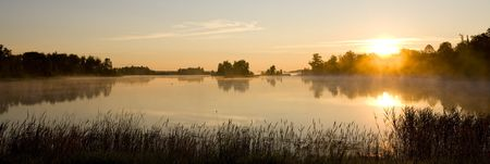 A minnesota morning as mist rolls off a small still lake. Stock Photo