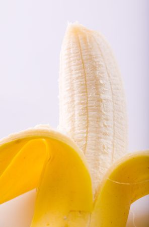 A peeled banana in a close up image on a white background