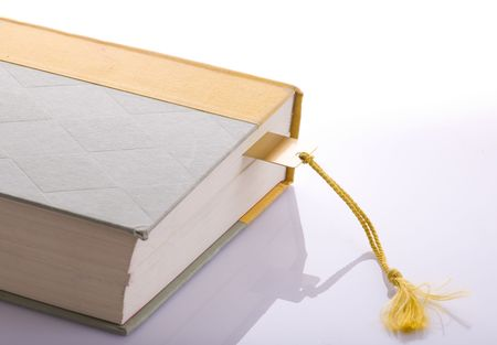 A book with a gold bookmark with a tassel on a background. Stock fotó